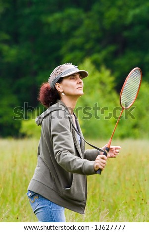 Woman with cap playing badminton in a meadow