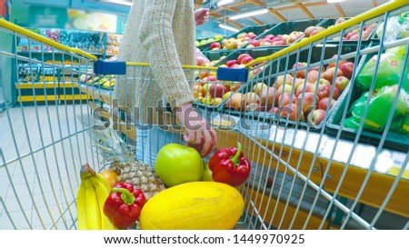 Woman with cart or trolley buying fresh vegetables and fruits at supermarket. Point of view shot. Consumerism, sale, shopping and health care concept