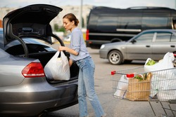 Woman with cart puts her purchases in car trunk