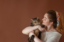 Woman with cat. cat in the hands of woman. Pet enjoys being in girls arms. Beautiful young girl holging fluffy cat. Bestfriends. Copy space. pets, comfort, rest and people concept
