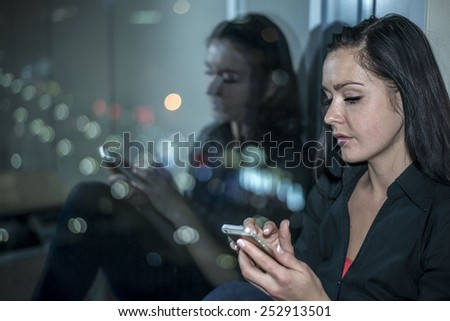 Woman with cell mobile telephone on background of night city. Reflection of face portrait on dark glass and colorful bokeh Light town Cute girl with long brunette hair read e-mail or look image book