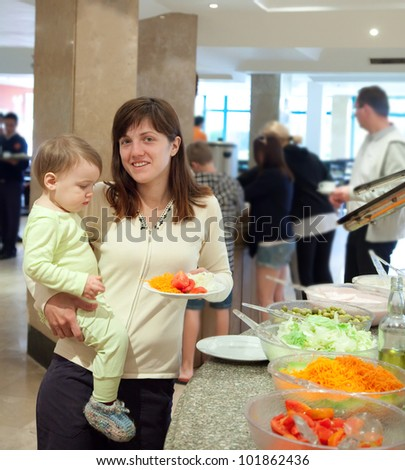 Woman with chid chooses  fresh vegetables  in buffet at hotel