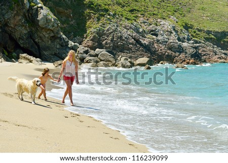 woman with child and dog on the beach