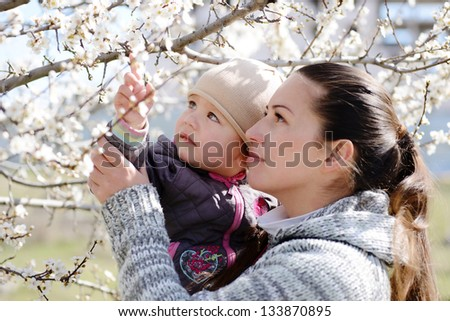 woman with child looking on  the blossom tree
