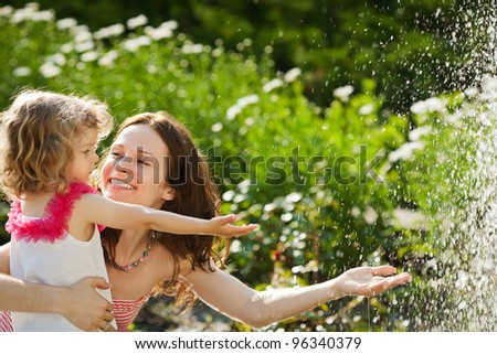 Woman with child playing against splashes of water in the summer