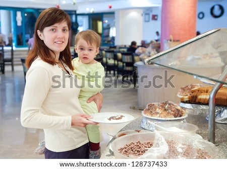 Woman with child  takes the meal on the buffet table