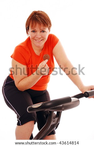 Woman with chocolate biscuit on exercise bike over white