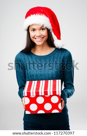 woman with christmas present and xmas hat having fun isolated on grey background