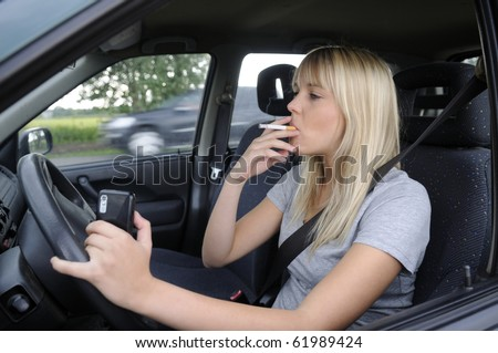 woman with cigarette and mobile phone in the car