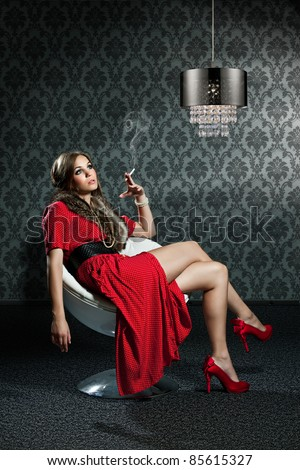woman with cigarette and red dress is sitting in front of a sixties wallpaper