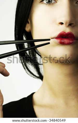 woman with classic  japanese make up on her lips and black chopstick