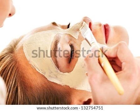 Woman with clay facial mask in beauty spa. Isolated.