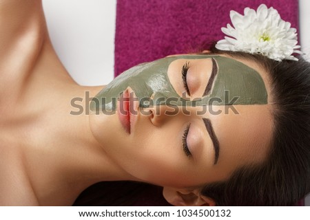 Woman with clay facial mask   in beauty spa. Skincare. Beauty Concept. Close-up portrait of beautiful girl with facial mask.Facial treatment. Cosmetology. Body care girl's