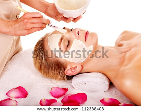 Woman with clay facial mask with rose petal. Isolated.