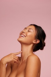 Woman with clean and clear skin smiling. Female model with eyes closed against pink background.