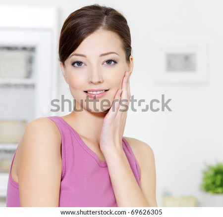 Woman with clean fresh skin of face looking at camera - indoors