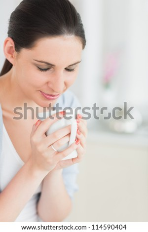 Woman with closed eyes holding a mug in a living room