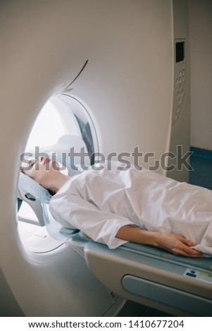 woman with closed eyes lying on computed tomography scanner table during radiology test #1410677204