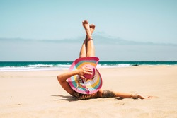 Woman with colorful hat enjoy the beach laying on the sand in summer holiday vacation travel lifestyle - young female caucasian people take a sunbath alone with blue ocean in background