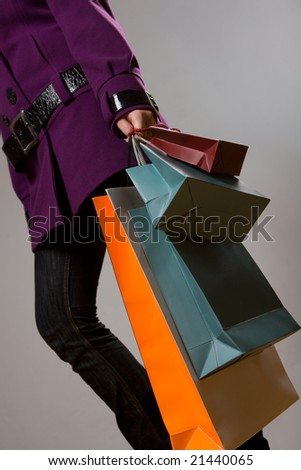 Woman with colorful shopping bags over grey