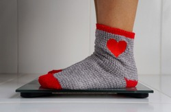 Woman with colorful socks weighing herself on a digital scale. Lose weight concept. Diet and health concept.