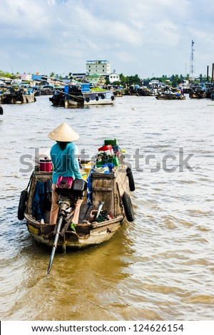 woman with conical hat driving her machine boat to floating market on Mekong river