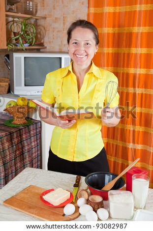 woman with cookbook and wire whisk in her kitchen