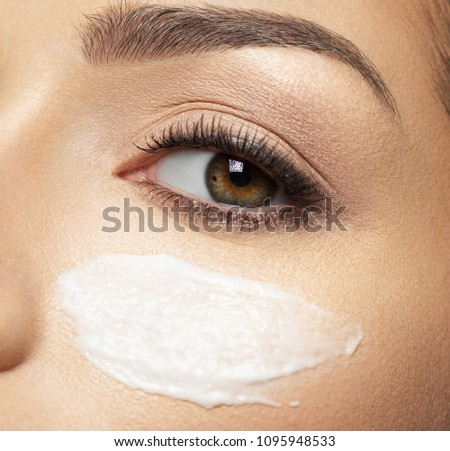 woman with cosmetic cream smear on face near eye.  Skin care  concept. Beauty treatment concept.
