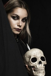 Woman with cranium and black background