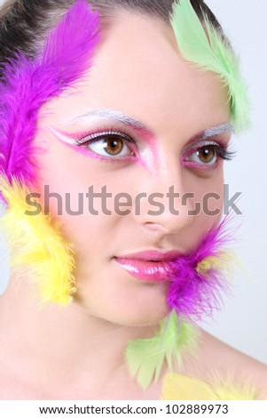 Woman with creative make-up and feathers like a bird