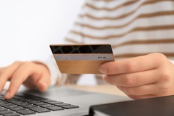 Woman with credit card and laptop at table, closeup. Internet shopping concept