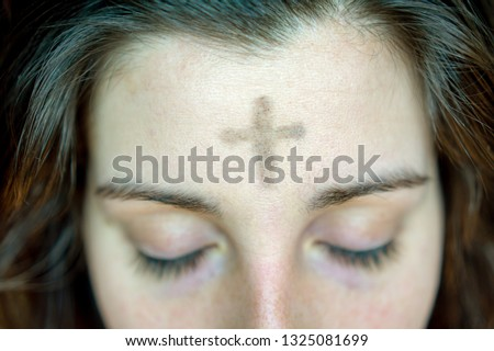 woman with cross on forehead in observance of Ash Wednesday religious concept #1325081699