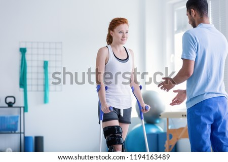 Woman with crutches during rehabilitation with helpful physiotherapist Foto stock ©
