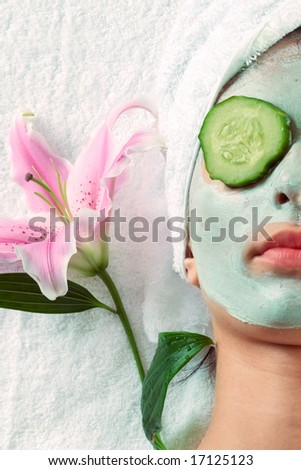 Woman with cucumbers and face mask