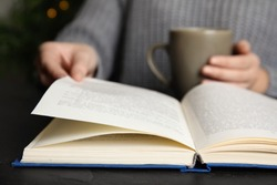 Woman with cup of beverage reading book at table, closeup