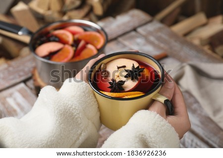 Woman with cup of delicious mulled wine at table, closeup Stockfoto ©