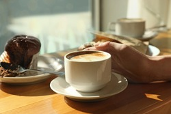 Woman with cup of fresh aromatic coffee at table in cafe