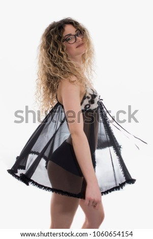 Woman with curly hair dressed in black babydoll posing on white background