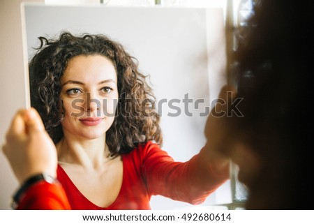 Woman with curly hair standing in front of  large mirror and smiling #492680614