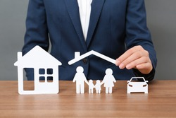 Woman with cutout paper family, house and car at table, closeup. Life insurance concept