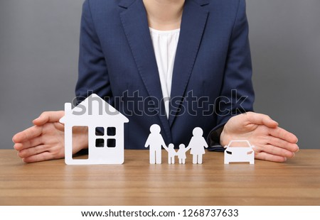 Woman with cutout paper family, house and car at table, closeup. Life insurance concept #1268737633