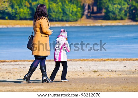 Woman with daughter walking in park in early spring