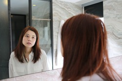 woman with decadent life face herself in the bathroom at morning