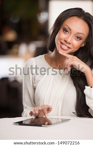 Woman with digital tablet. Beautiful African descent women working on digital tablet and smiling