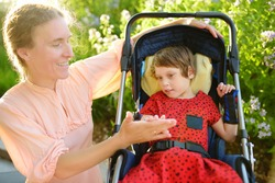 Woman with disabled girl in a wheelchair walking in the summer park. Child cerebral palsy. Disability. Inclusion. Means of rehabilitation. Orthosis. Family with disabled kid.