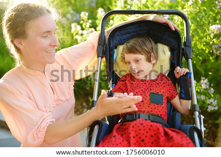 Woman with disabled girl in a wheelchair walking in the summer park. Child cerebral palsy. Disability. Inclusion. Means of rehabilitation. Orthosis. Family with disabled kid. Stock photo ©