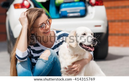 woman with dog by car full of suitcases. car trip. Woman and dog in car on summer travel. getting ready for road trip.
