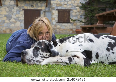Woman with dog lying on the green grass in the park. great dane dog breed