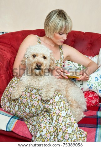 woman with dog reading book while sitting on the sofa at home living room