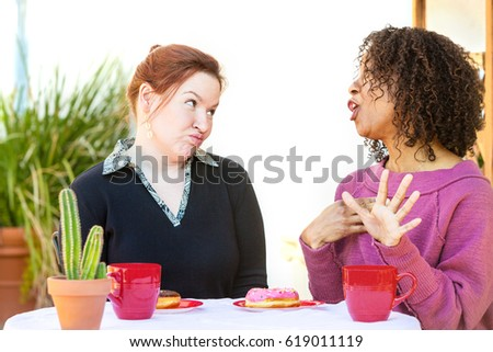 Woman with doubtful expression listening to friend talking at table